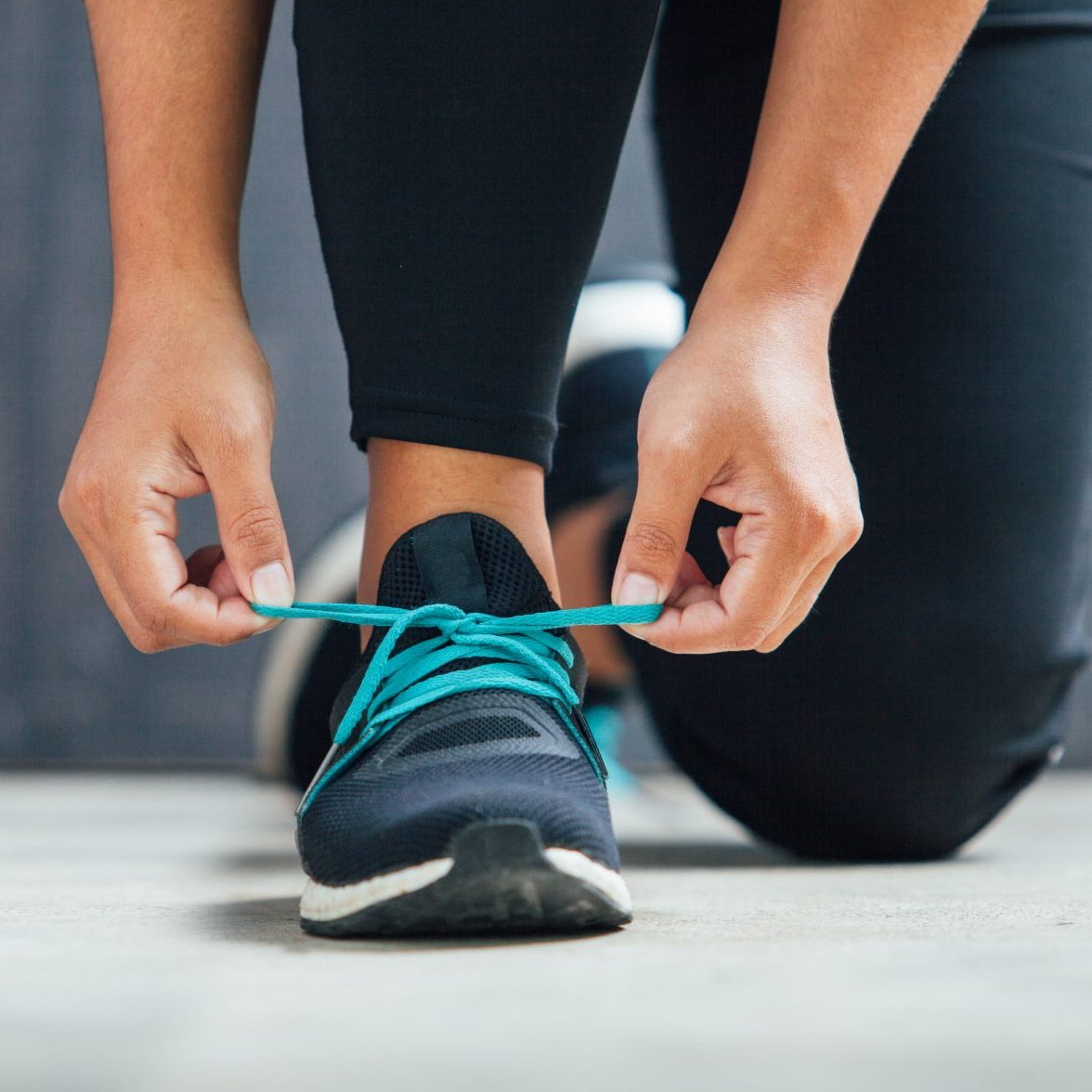 Female runner tying her shoes preparing for a run